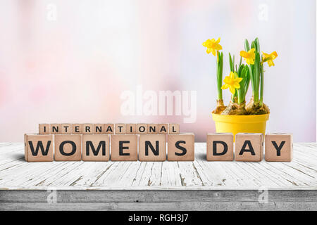 International Womens day sign with a yellow daffodil flower on a wooden desk with a pink background - Stock Image