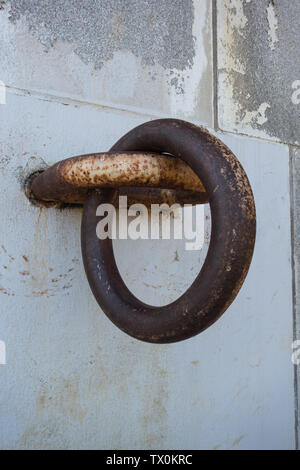 Anchor with ring on concrete bulkhead used to tie up a boat - Stock Image