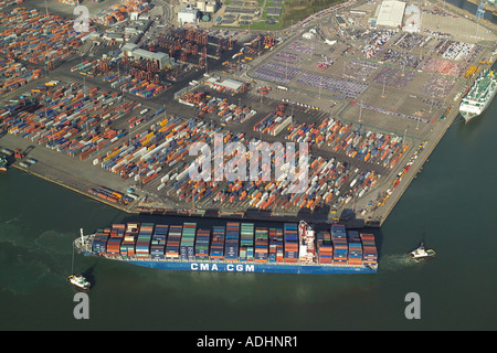 Aerial view of a Container Ship at Southampton Container Terminal being manouvered into position by two tug boats - Stock Image