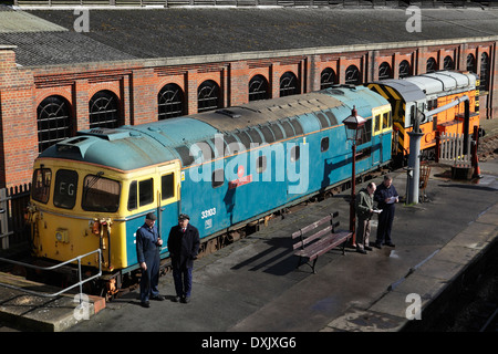 Class 33/1 33103 'Swordfish' and Class 9 09018 beside engine sheds and platform at Sheffield Park station, Bluebell Railway - Stock Image