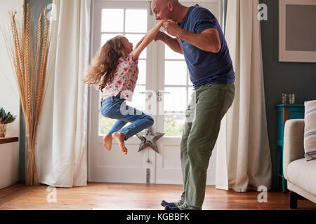 Girl jumping in the air at home holding dad's hands - Stock Image