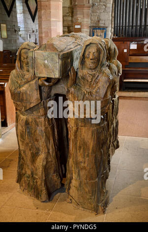 Wood sculpture of monks carrying dead brother in coffin in The Parish Church of Saint Mary the Virgin on Holy Island of Lindisfarne England UK - Stock Image