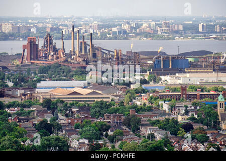 Hamiilton residential areas in forground, steel mills in industrial sectors along waterfront skyline with highway QEW or Queen Elizabeth Way over Lake - Stock Image