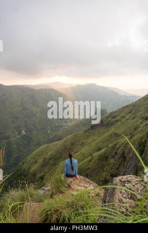Woman sitting on the top of Small Adams peak near Ella, Sri Lanka - Stock Image