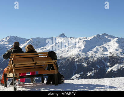 The swiss ski and snow-sport linked resort of St Luc and Chandolin in the Valais region of Switzerland.  Skiers relaxing and looking towards Grimentz - Stock Image