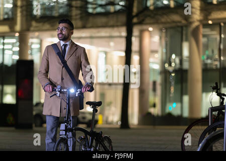Businessman with bicycle on urban street at night - Stock Image