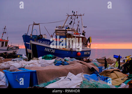 Hastings,  East Sussex, UK. 26th Dec, 2018. A brief glimpse of the sun on the fishing boat beach at sunrise on a mild overcast Boxing Day morning. - Stock Image
