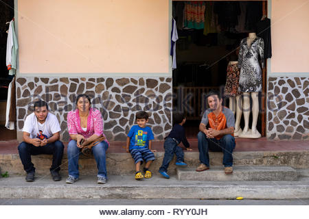 Shop-keeping family with children and merchandise showing through an open door. - Stock Image