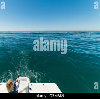 Boy fishing on sailboat - Stock Image