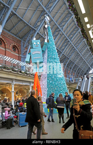 Tiffany & Co Christmas tree and robot & woman taking selfie in shopping mall area at St Pancras International Railway Station London UK  KATHY DEWITT - Stock Image