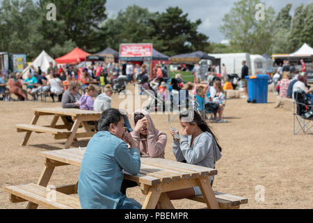 Poole, UK. 28th July 2018. People enjoy the rides, food stalls and live music at the Poole Harbour Festival in very windy weather. Credit: Thomas Faull/Alamy Live News - Stock Image