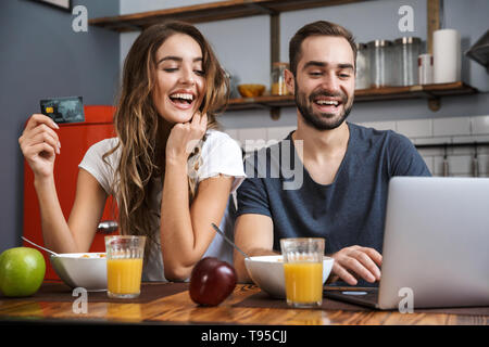 Cheerfuly young couple shopping with laptop and credit card while having breakfast - Stock Image