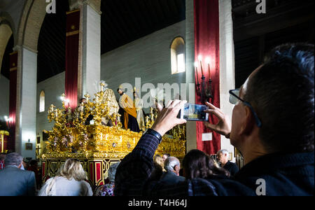 Man taking a cellphone photo of a special Holy Week gold altar showing a biblical scene inside a church in Seville - Stock Image