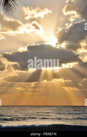 Colorful, partially cloudy orange sunset with sun rays piercing the clouds over the Atlantic Ocean as seen from Florida, USA. - Stock Image