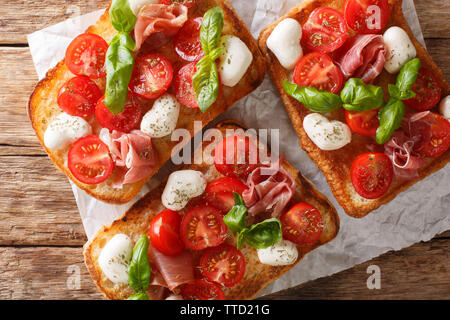 Ciabatta sandwiches with mozzarella, tomatoes, ham and basil close-up on the table. Horizontal top view from above - Stock Image