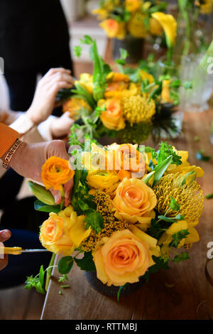 Making flower bouquets at floral arrangement party learning how to assemble flowers - Stock Image