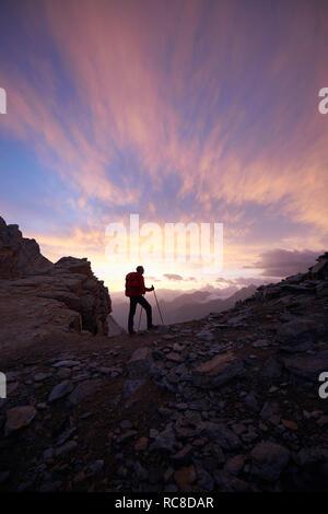 Hiker admiring sunset, Mont Cervin, Matterhorn, Valais, Switzerland - Stock Image