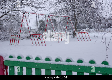 Swings covered in snow at empty children's playground - Stock Image