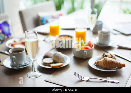 Glass of champagne on breakfast table in restaurant - Stock Image