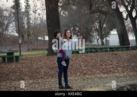 A mother points to something for her daughter as she sits in her mother's arms in Plaza Park in Visalia, CA. - Stock Image