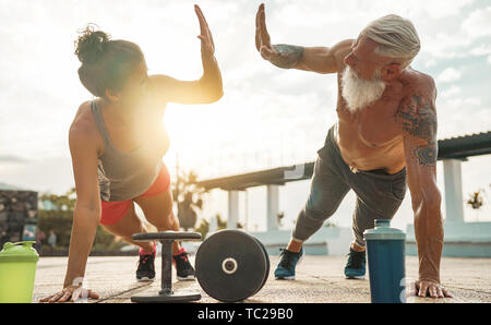 Fitness couple doing push ups exercise at sunset outdoor - Happy athletes making gym workout session outside - Stock Image