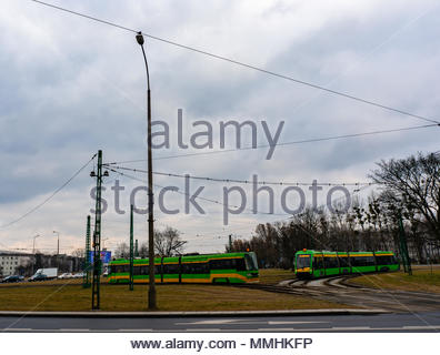 Two public transport trams driving on the Rataje roundabout on a cloudy day in Poznan, Poland - Stock Image