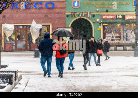 A number of people walk in snow carrying an umbrella, Wrocław, Wroclaw, Wroklaw, Poland - Stock Image
