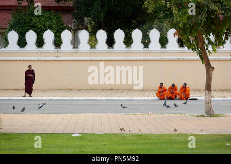 Comical street shot of young buddhist monks at opposite ends of the frame in front of the Royal Palace in Phnom Penh, Cambodia. - Stock Image