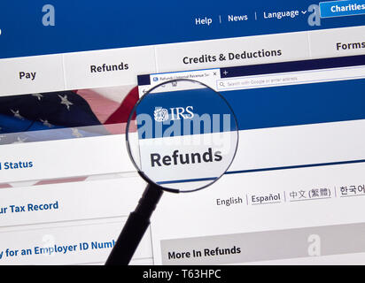 MONTREAL, CANADA - APRIL 24, 2019 : IRS Refunds USA Government home page under magnifying glass. IRS.com is an official web site of Internal Revenue S - Stock Image