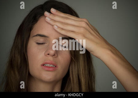 Young woman holding hand on forehead with eyes closed - Stock Image