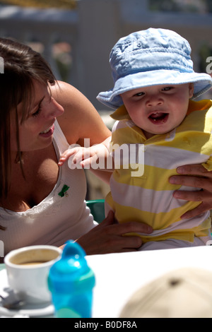 Mother and Toddler sitting at outdoor table wearing blue sunhat, biscuit crumbs on lips - Stock Image