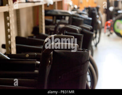 Black wheelchairs with handles lined up in a teaching clinic or ready for use in a hospital - Stock Image