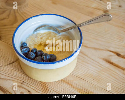 Breakfast dish oatmeal porridge in a stoneware bowl with milk blueberries and honey on a wooden table top - Stock Image