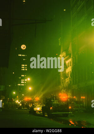 Emergency vehicles at the scene of a fire in New York City at night ca. 1965 - Stock Image