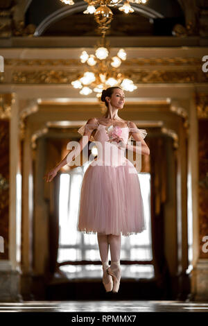 Beautiful ballerina dancing and jumping in a luxurious hall with a chandelier in a pink dress against the window. - Stock Image