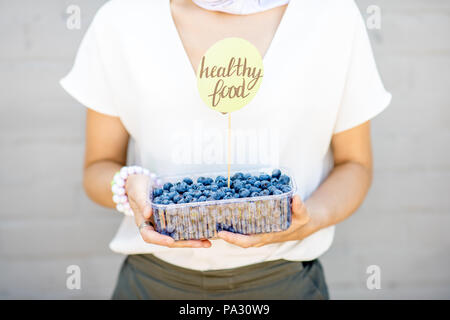 Woman holding box with blueberries and green sticker on the gray wall background - Stock Image