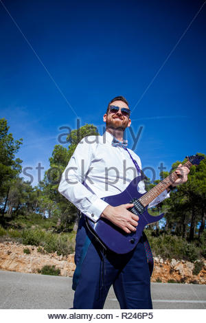 A young man with a red beard and an elegant dress holds an electric guitar in a forest. - Stock Image