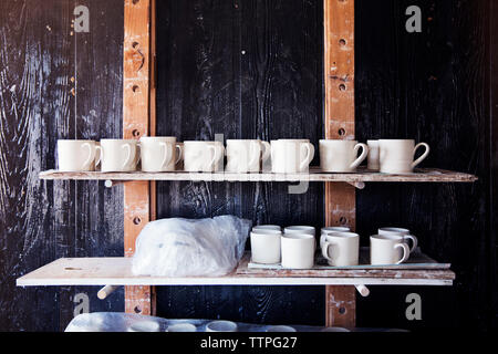 Clay mugs on shelves at workshop - Stock Image