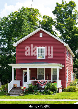 COUDERSPORT, PA, USA-10 AUGUST 18:  A red 2-story shotgun-style house with manicured lawn on the main street of the small rural town. - Stock Image