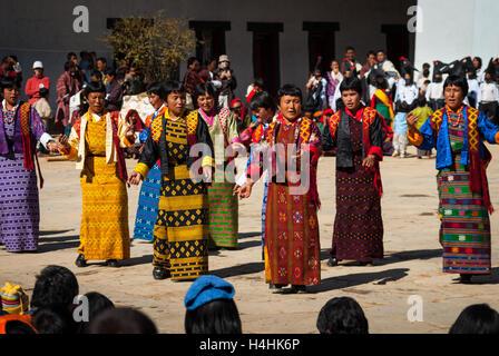 Ladies wearing traditional kira performing folk dance at Black-necked Crane Festival, Gangte Monastery, Phobjikha - Stock Image