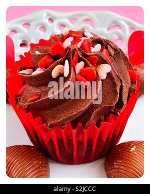 Chocolate cupcake on a vintage blue plate. Pink Background. - Stock Image