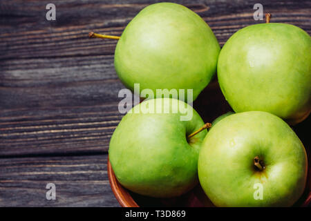 Beautiful ripe apples green in a bowl on a wooden table top view - Stock Image