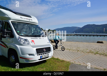 Woman on a bicycle on the promenade cycling beside  the shores of Ossiacher See , Austria. Europe - Stock Image