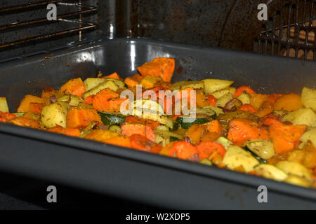 inside oven with baked oven vegetables as garnish, crispy grilled vegetarian and vegan oven vegetables seasoned with herbs and olive oil - Stock Image