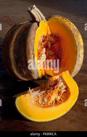 A squash or gourd with a slice which has just been removed from it. Vertical, colour - Stock Image