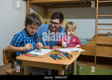 Brothers enjoying to draw with colored pencils while father is smiling, Munich, Germany - Stock Image