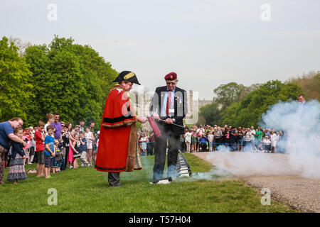 Windsor, UK. 22nd April 2019. John Matthews, borough bombardier, supervises Cllr Paul Lion, Mayor of Windsor and Maidenhead, in firing a small cannon as part of a traditional 21-gun salute on the Long Walk in front of Windsor Castle for the Queen's 93rd birthday. The Queen's official birthday is celebrated on 11th June. Credit: Mark Kerrison/Alamy Live News - Stock Image