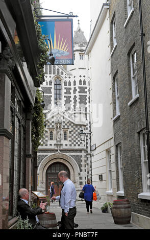 Men drinking beer outside The Rising Sun pub with a view of St Bartholomew the Great church in Smithfield London EC2 England UK  KATHY DEWITT - Stock Image