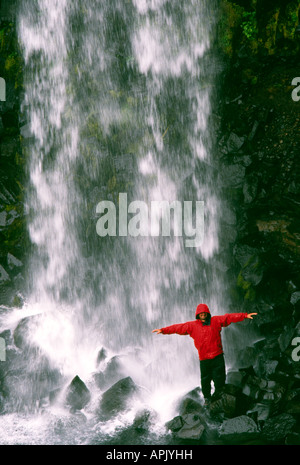 Carl Galvin in a red Mountain Equipment gore tex jacket under Svartifoss Waterfall in Iceland - Stock Image