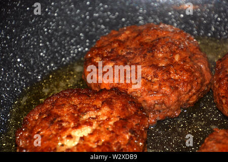 ready to eat crispy meatloaf, crispy meatballs fry in oil in a pan detail and macro shot - Stock Image